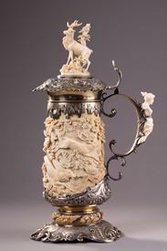 A SILVER MOUNTED RELIEF CARVED IVORY TANKARD.<br/>